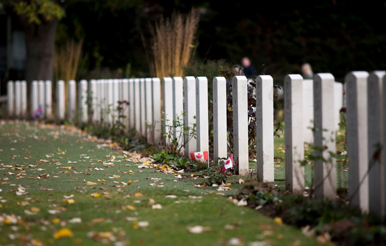 CANADIAN FLAGS ON A GRAVE AT ESSEX FARM CEMETERY, YPRES, BELGIUM